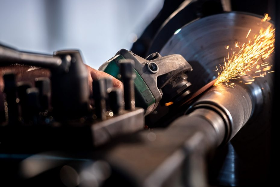 Mechanic is using electric grinding wheels on steel structures i